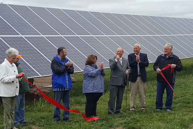 Group of people clap as they cut ribbon near large solar project